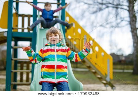 Two little kid boys having fun and sliding on outdoor playground. Funny children, friends and siblings smiling and climbing on slide. Summer, spring and autumn leisure for active kids.