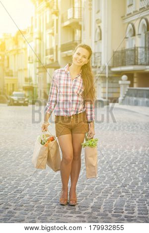 Beautiful woman in full lenght with bags in her hands. Lady with lond red hair carrying bags full of fruits and vegetables. Toned image.