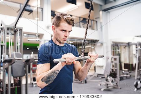 Young handsome fit man working out on pull-down machine in gym. Bodybuilder exercising with cable weight machine.