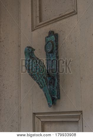 Brass Knocker In The Shape Of A Bird On A Cream-colored Door, A Beautiful Combination Of Green With