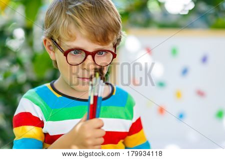 Confused little kid boy with glasses holding watercolors and brushes. Happy child and student is back to school. Education, school, learning concept. School, preschool nursery equipment