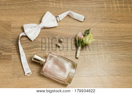 Wedding accessories. Pink perfume, bridal earrings with diamonds, white bowtie and boutonniere with small roses and a wooden background