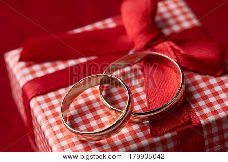 Close-up of two gold Wedding rings and Gift box for wedding with red bow on velvet red background with copyspace. Love and marriage proposal concept.