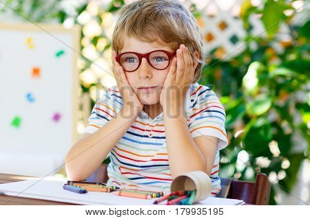 Confused little kid boy with glasses with colorful wax crayon pencils. Sad child and student is back to school. Education, school, learning concept. School, preschool nursery equipment