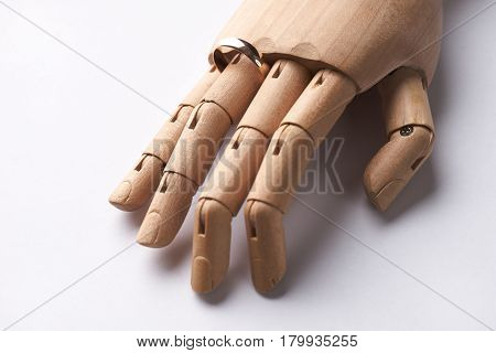 Prosthetic Wooden Hand with wedding ring on ring-finger isolated on white background.