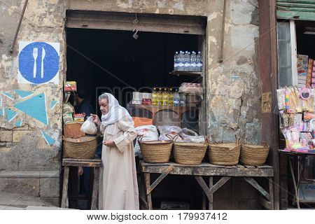 CAIRO, EGYPT - JANUARY 23, 2016: A traditional small shop and customer in traditional clothes in Capital City Cairo, Egypt.