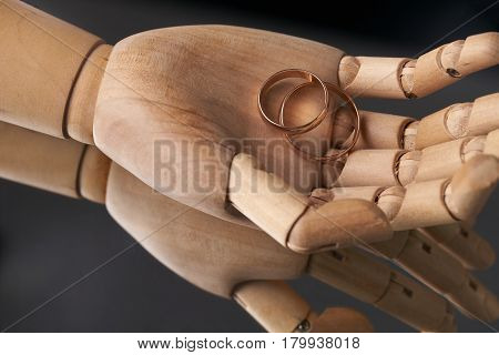 Prosthetic Wooden Hands with two wedding rings On a mirror background.