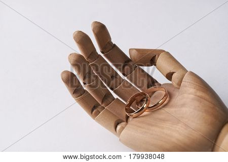 Prosthetic Wooden Hands with two wedding rings isolated on white background.