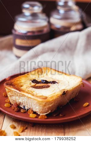 Organic curd casserole with raisins and figs nuts on a wooden background with a glass of milk. Fat cheesecake and a glass of milk.
