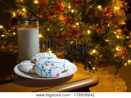 Cookies and milk on a table next to a lit Christmas tree