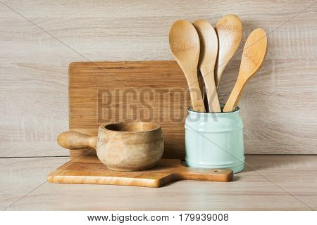 Wooden rustic and vintage crockery tableware utensils and stuff on wooden table-top. Kitchen still life as background for design. Image with copy space.