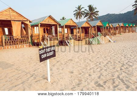 Wooden cottage and cabins of sandy beach resort with sign Dont Disturb Our Guests.