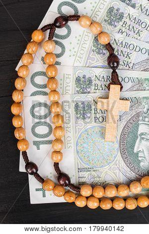 Closeup of a wooden rosary on Polish banknotes