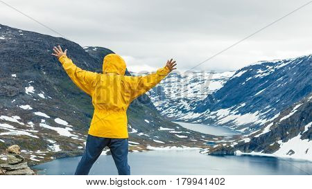 Tourism holidays and travel. Man tourist standing near Djupvatnet lake relaxing meditation with serene mountains view Stranda More og Romsdal Norway Scandinavia. poster