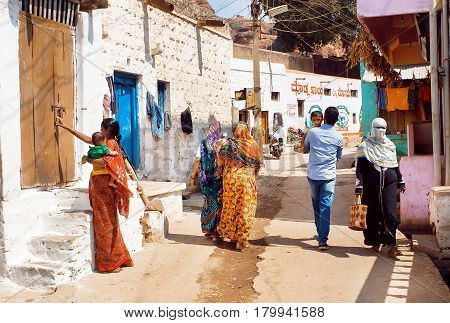 BADAMI, INDIA - FEB 8, 2017: Many people walking on narrow street with brick rural houses of small town in Karnataka state on February 8, 2017. Population of Karnataka is 62000000 people
