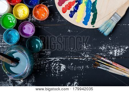 Artist's workshop. Canvas, paint, brushes, palette knife lying on the table.Art tools.Artist workplace background.Acrylic paint and brushes.Art picture with copy space and for add text.