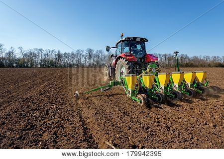 Agriculture tractor sowing seeds and cultivating field.