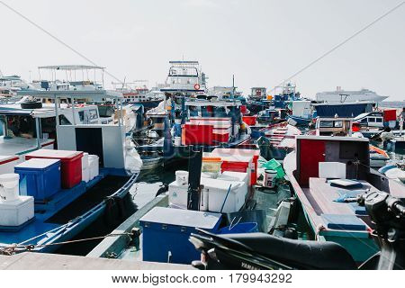 Male, Maldives - December 17, 2016: Fishing boats in the harbor in city Male capital of Maldives