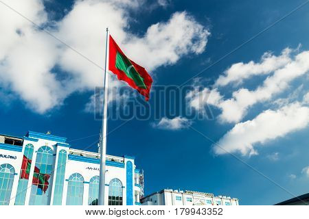 Male, Maldives - December 17, 2016: Shaheedh Hussain Adam Building And Flag Of Maldives In Centre Of