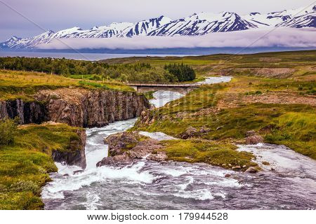 The rapid cold creek flows among the flat tundra. The concept of extreme northern tourism. On the horizon - rhyolite mountains in the snow