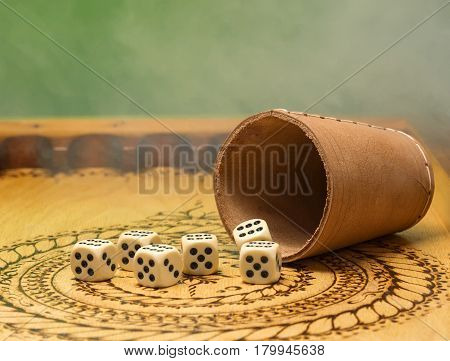image of elements of gambling on a carved wooden board,Figures five, green background, smoke