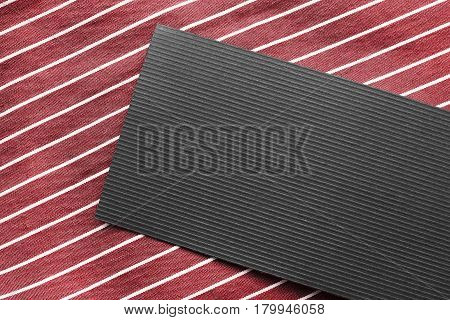 Blank black label on red striped cloth as a background