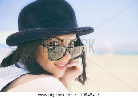 Portrait of smiling beautiful young woman in black hat. Model shooting on the beach.