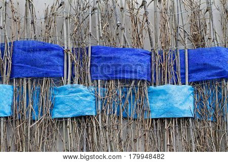 Background of twigs with interwoven wide blue ribbons of felt