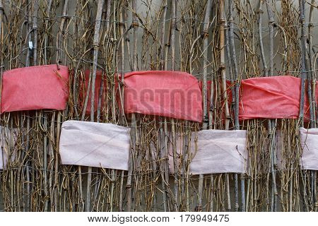 Background of twigs with interwoven wide red and white ribbons of felt