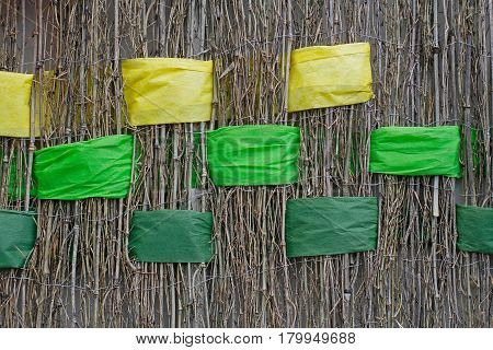 Background of twigs with interwoven wide yellow and green ribbons of felt