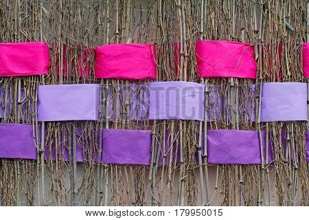 Background of twigs with interwoven wide pink and violet ribbons of felt