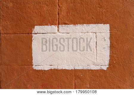 Orange concrete blocks wall with painted splotch as background or texture