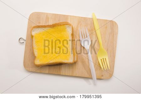 sweet toast butter on wooden chopping board with color fork on white background. this bread is thai style sweetmeat.