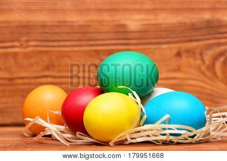 Painted Easter Colorful Eggs With Straw Nest On Wooden Background