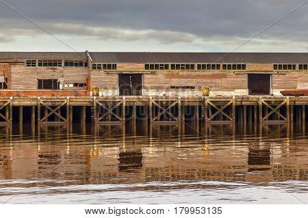 Old Wooden Harbor Buildings in Delfzijl under orange evening light