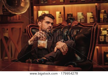Confident upper class man with glass of beverage in gentlemen's club