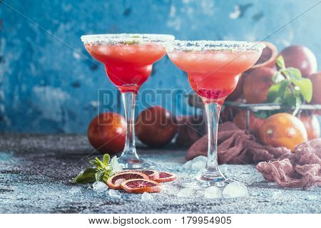 Blood Orange Margarita cocktail with mint and red orange in salt rimmed cocktail glass with tequila syrup and crushed ice