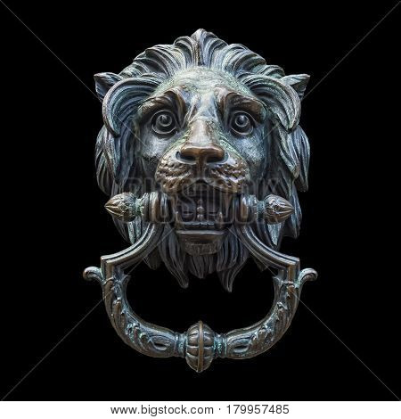 A classic lion head door knocker made out of metal and isolated against a black background.