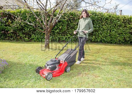 Middle-aged Woman Passes The Lawn Mower In The Garden