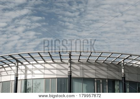 Clouds over the building. Unusual office architecture.