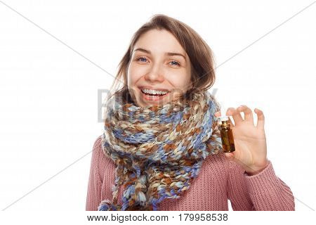 Young smiling female in scarf showing bottle with nasal drops isolated on white background.