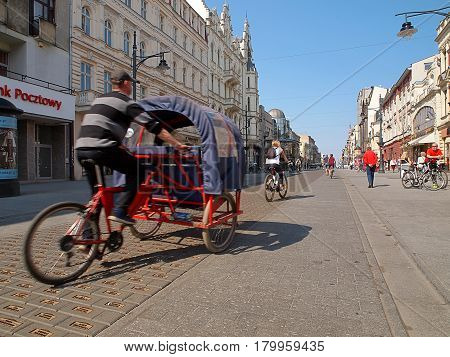 Rickshaws on the street Piotrkowska. Lodz, Poland - April 02, 2017 Rickshaws with tourists, cyclists and historic buildings on the street Piotrkowska.