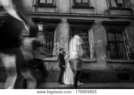 Romantic newlywed couple holding hands near old building in France crowd in foreground bride and groom together portrait romance story concept time stands still
