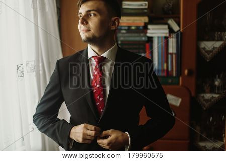 Handsome groom in white shirt with red tie buttoning up black suit morning wedding preparation businessman in suit looking out the window