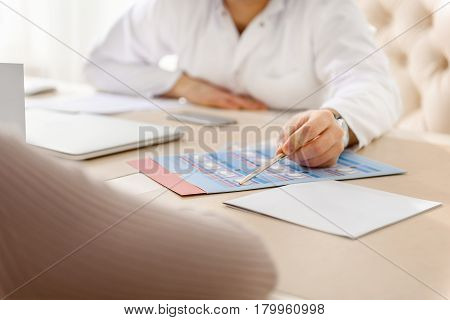Please, filling in form. Focus on close up doctor arm showing blank to client. Hospital reception concept
