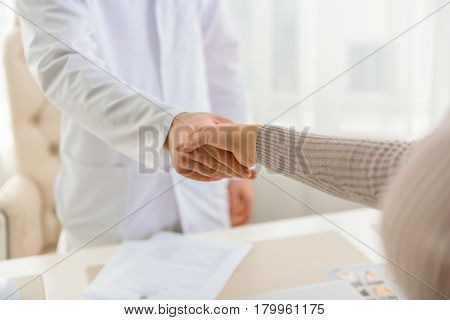 Close up of shaking hands. Woman expressing gratitude to physician for cure