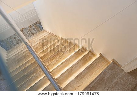 Wide wooden staircase descending to marble tile. Interior concept