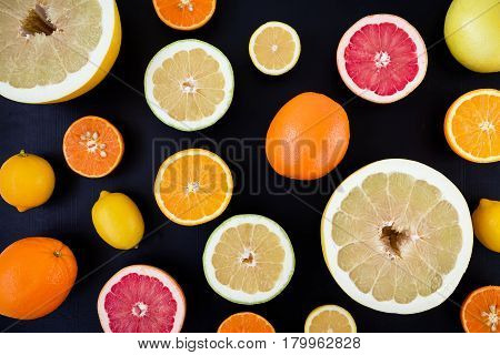 Lemon, orange, mandarin, grapefruit and sweetie on dark background. Flat lay, top view. Fruit background