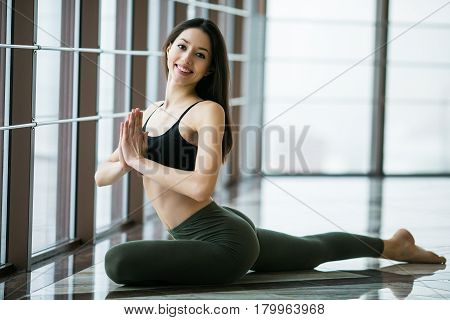 Kapotasana. Beautiful Yoga Woman Practice In A Big Window Hall Background. Yoga Concept.