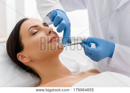 Doctor hand drawing correction marks on face of unconcerned woman. She lying in bed in surgical clinic